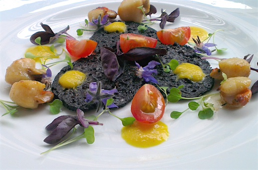 Grilled queen scallops with black pudding, yellow bell pepper dressing and micro herbs